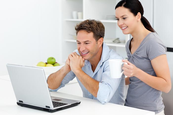 homme et femme heureux devant l'écran de l'ordinateur