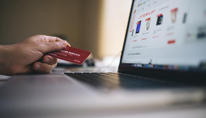 main avec carte de crédit devant clavier ordinateur
