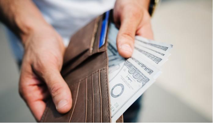 homme montrant son portefeuille rempli d'argent grace aux meilleures facons de gagner de l'argent à domicile ou sur internet